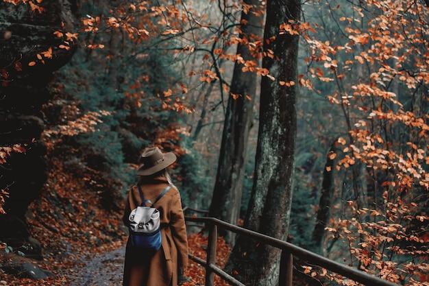 Jovem mulher com chapéu em um parque de temporada outono