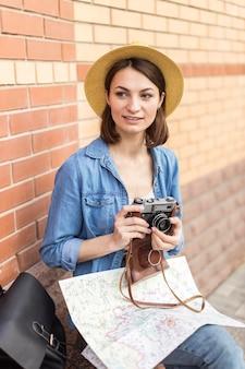 Jovem mulher com chapéu segurando a câmera
