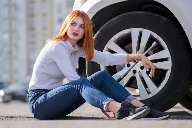 Jovem mulher com chave esperando ajuda para mudar a roda em um carro quebrado.