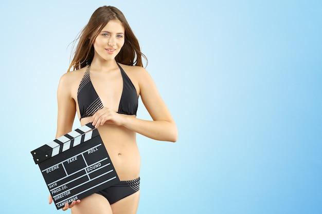 Jovem mulher com claquete de cinema em biquíni