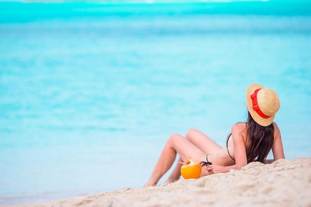Jovem mulher com coco no biquini que aprecia o sol que sunbathing pelo oceano perfeito de turquesa.