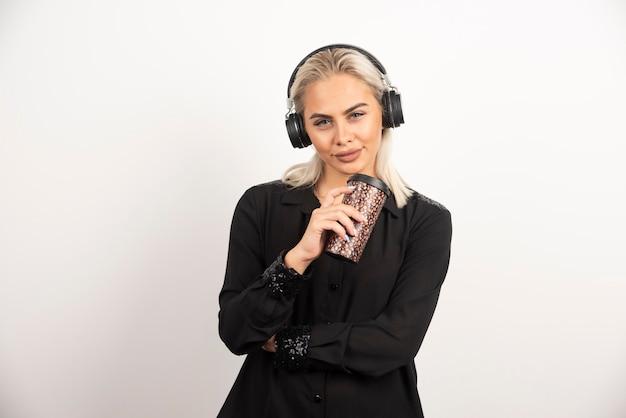 Jovem mulher com copa em fones de ouvido em uma parede vermelha.