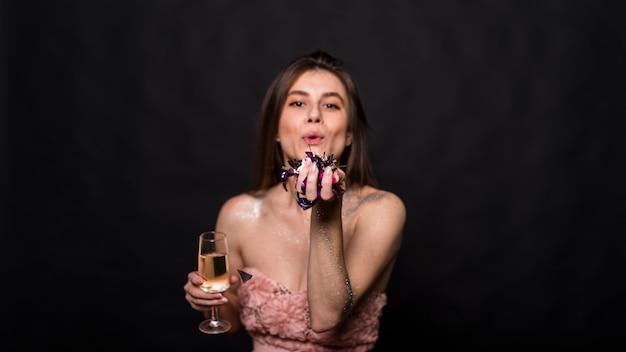 Jovem mulher com copo de bebida e plantas na mão mandando beijo