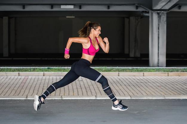 Jovem mulher com corpo apto pulando e correndo