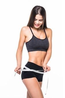 Jovem mulher com corpo bonito, medindo a coxa com tipo de medição após dieta, isolada no branco
