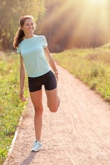 Jovem mulher com corpo magro perfeito, esticando a perna dela