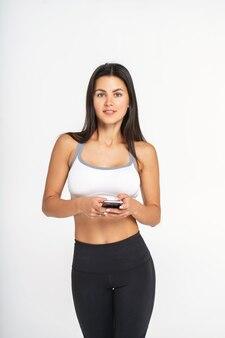 Jovem mulher com corpo saudável magro bonito posando no estúdio com telefone em suas mãos.