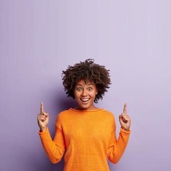 Jovem mulher com corte de cabelo afro e suéter laranja