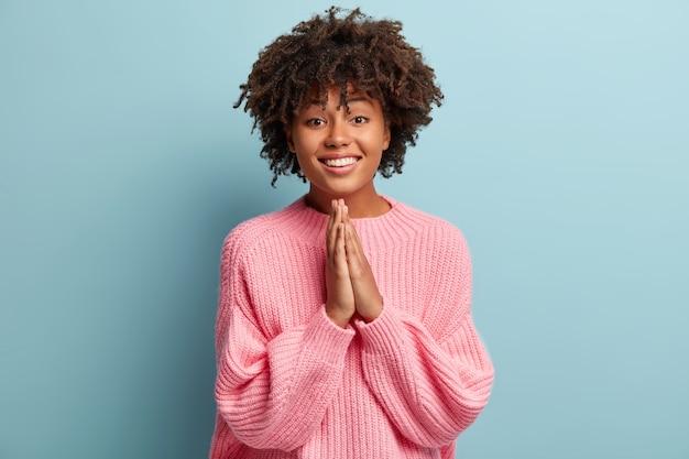 Jovem mulher com corte de cabelo afro e suéter rosa