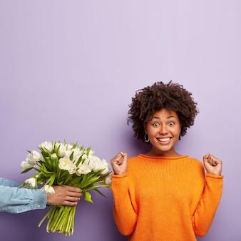 Jovem mulher com corte de cabelo afro recebendo buquê de flores brancas