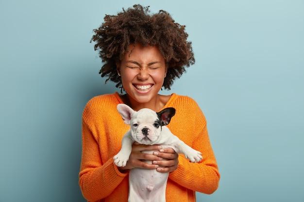 Jovem mulher com corte de cabelo afro segurando um cachorrinho