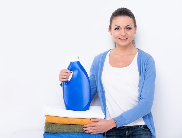 Jovem mulher com detergente e lavanderia.