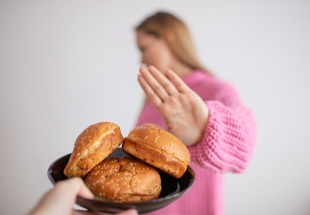 Jovem mulher com dieta sem glúten está dizendo não, graças ao pão