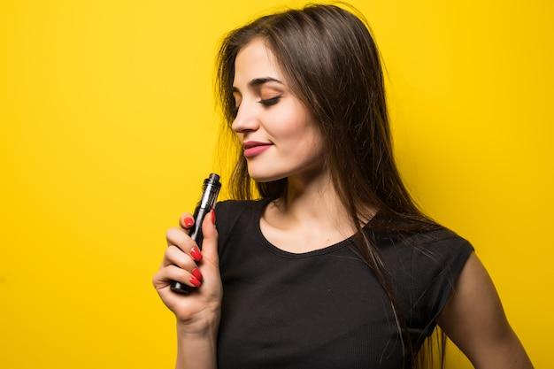 Jovem mulher com dispositivo de fumaça vape em pé na parede amarela