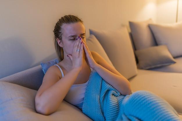 Jovem mulher com dor de cabeça, sniffle e sinusite.