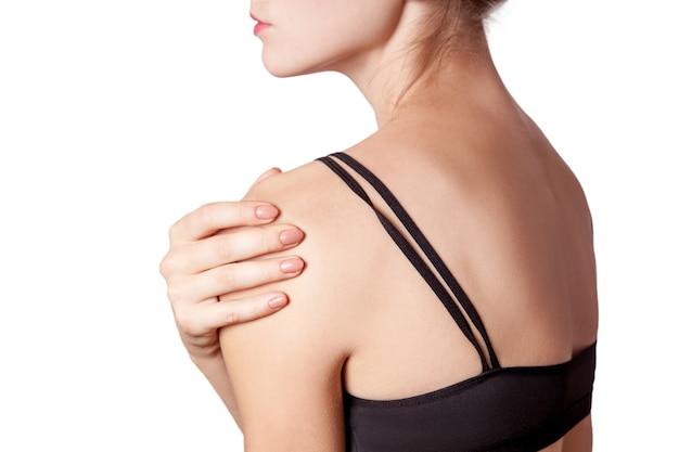 Jovem mulher com dor no braço e ombro em fundo branco.
