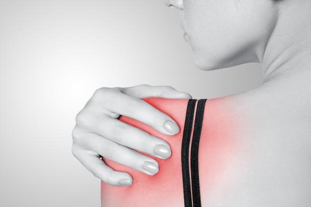 Jovem mulher com dor no braço e ombro em fundo cinza. foto em preto e branco com ponto vermelho.