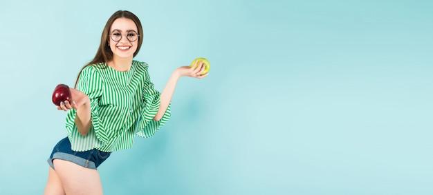 Jovem mulher com duas maçãs