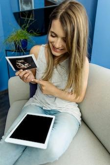 Jovem mulher com ecografia e tablet