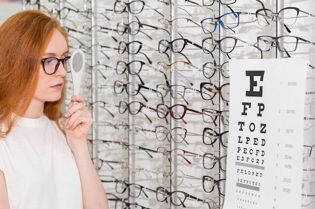 Jovem mulher com espetáculo segurando oclusor na frente dos olhos enquanto lê o gráfico de snellen na clínica oftalmológica