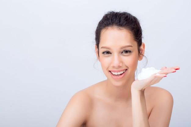 Jovem mulher com espuma de limpeza para cuidados com a pele no fundo branco