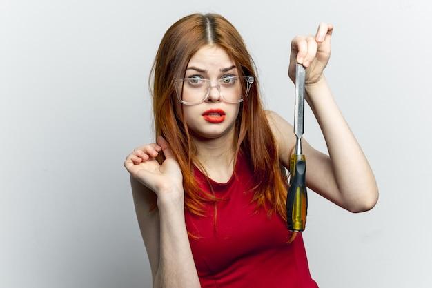 Jovem mulher com ferramentas de construção nas mãos dela, reparação