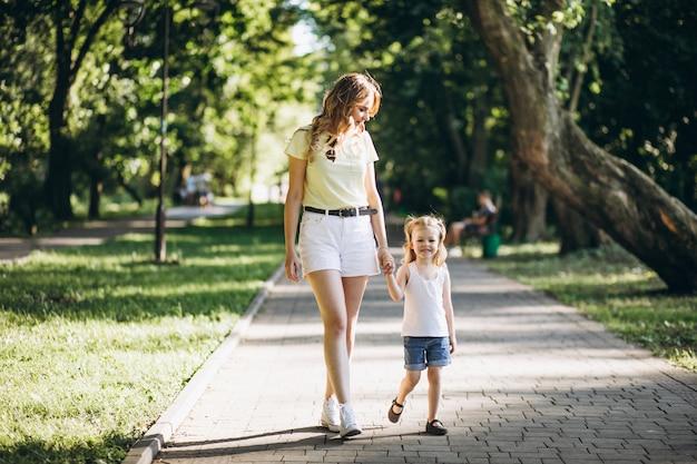 Jovem mulher com filha caminhando no parque