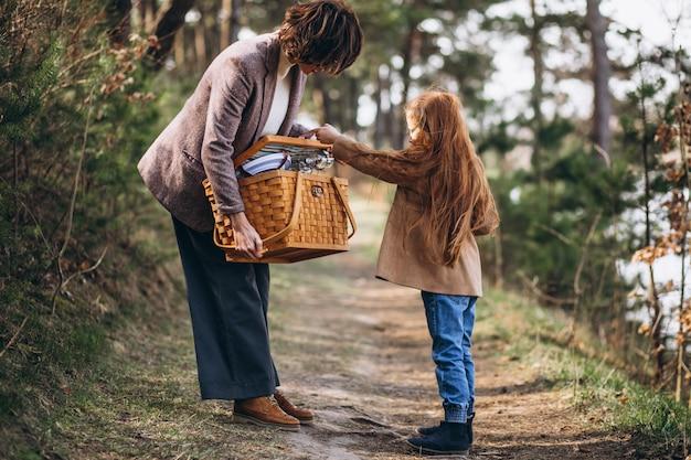 Jovem mulher com filha na floresta com caixa de piquenique