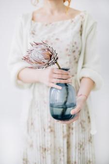 Jovem mulher com flor protea em um vaso azul.
