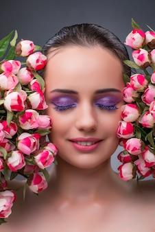 Jovem mulher com flores no conceito de beleza
