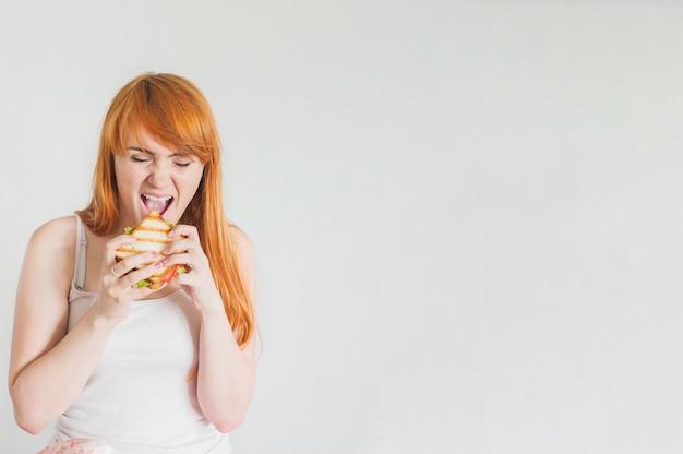 Jovem mulher com fome que come o sanduíche grelhado contra o fundo branco
