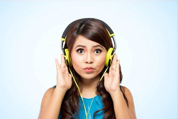 Jovem mulher com fone de ouvido amarelo, isolado