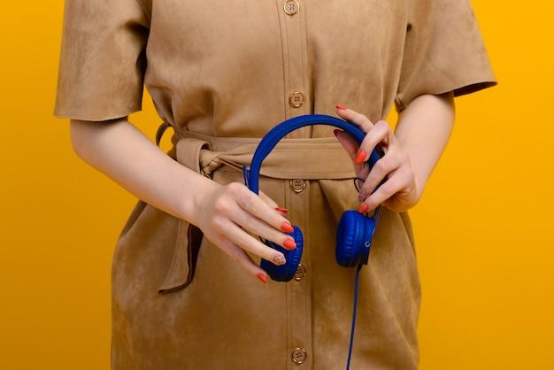 Jovem mulher com fones de ouvido azuis nas mãos no espaço amarelo