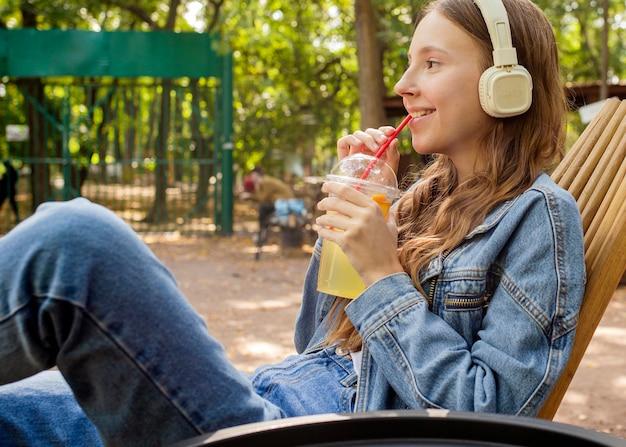 Jovem mulher com fones de ouvido bebendo suco fresco