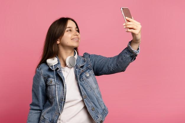 Jovem mulher com fones de ouvido, leva selfie, posa para câmera isolada em rosa