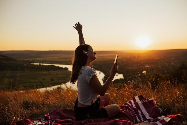 Jovem mulher com fones de ouvido, ouvindo música e curtindo o lindo pôr do sol
