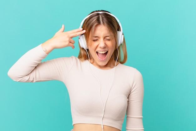 Jovem mulher com fones de ouvido, parecendo infeliz e estressada, gesto suicida fazendo sinal de arma