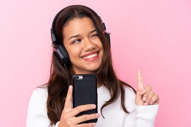 Jovem mulher com fones de ouvido sobre parede rosa