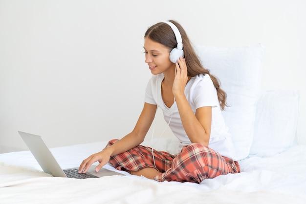 Jovem mulher com fones de ouvido trabalhando em casa usando um laptop