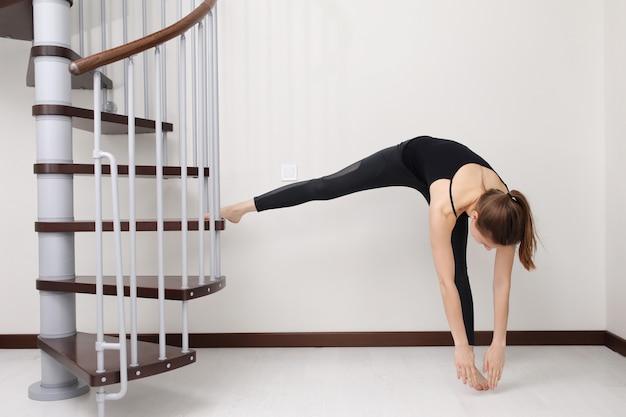 Jovem mulher com forma de corpo esbelto no sportswear fazendo exercício