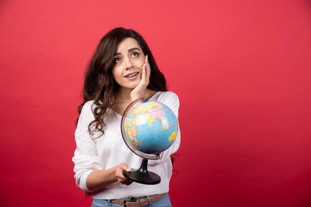Jovem mulher com globo sonhando com viagens sobre fundo vermelho. foto de alta qualidade
