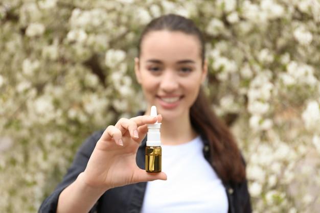 Jovem mulher com gotas nasais perto de árvore florescendo. conceito de alergia