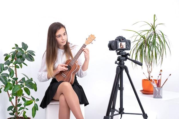 Jovem mulher com guitarra criando conteúdo on-line em fundo branco com espaço de cópia