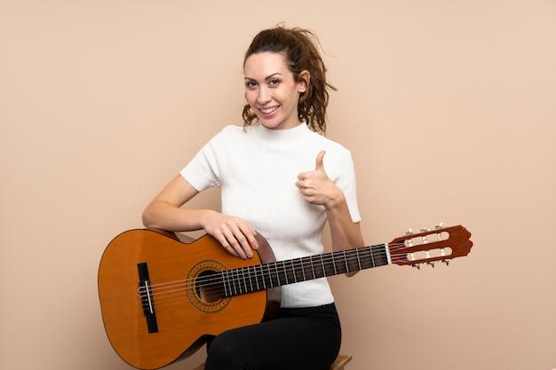 Jovem mulher com guitarra isolada demais com polegares para cima porque algo bom aconteceu