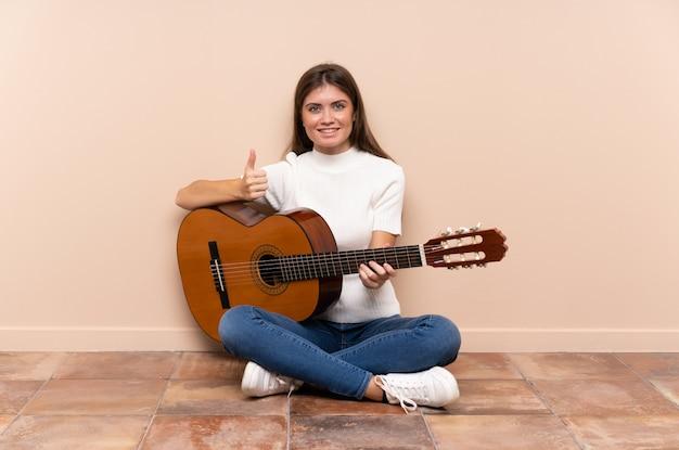 Jovem mulher com guitarra, sentada no chão, dando um polegar para cima gesto