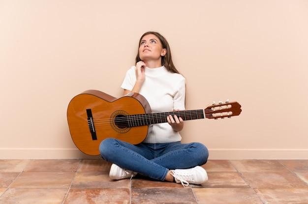 Jovem mulher com guitarra, sentada no chão, pensando em uma idéia