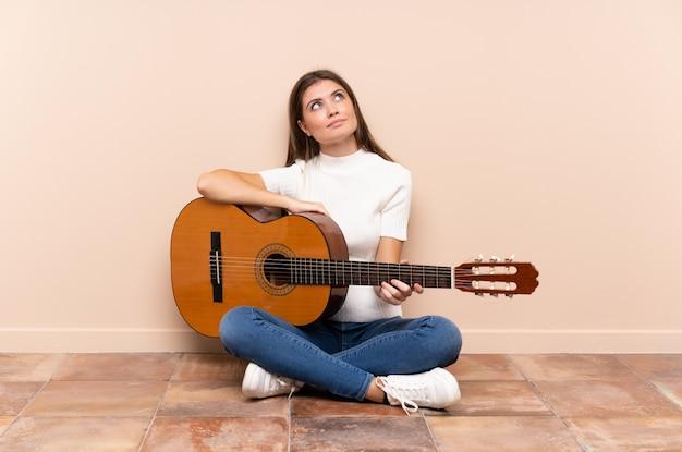 Jovem mulher com guitarra, sentada no chão, rindo e olhando para cima