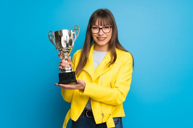 Jovem mulher com jaqueta amarela na parede azul, segurando um troféu