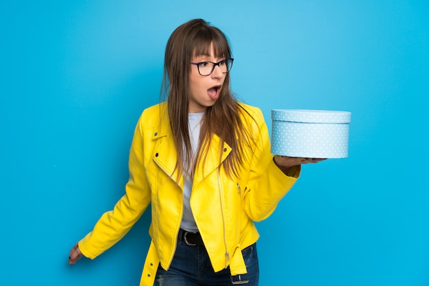 Jovem mulher com jaqueta amarela, segurando a caixa de presente nas mãos