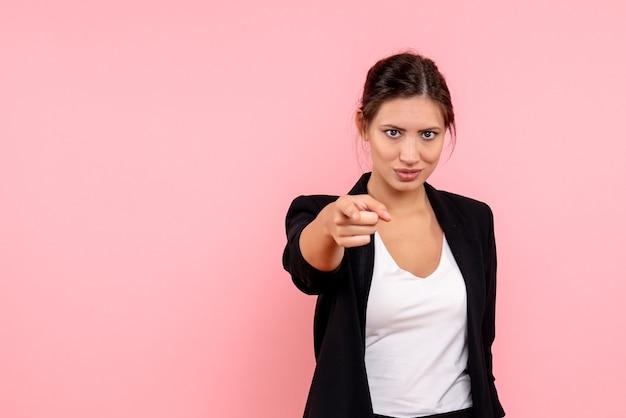 Jovem mulher com jaqueta escura, vista frontal, apontando no fundo rosa